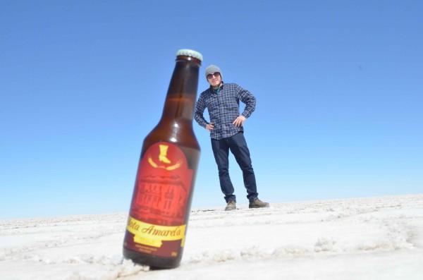 Guilherme em uma foto com sua cerveja artesanal Bota Amarela em Uyuni