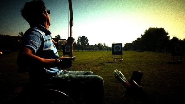 usuario de silla de ruedas lanzando flecha